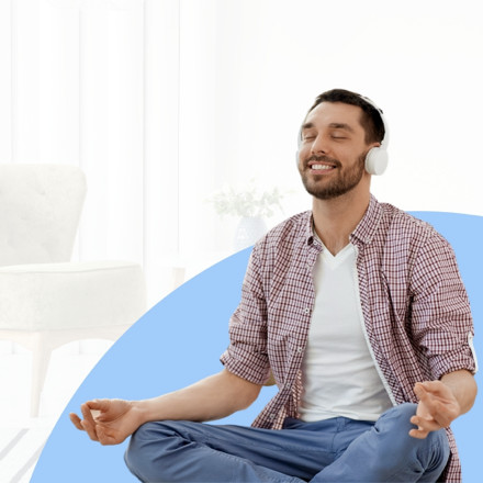a man meditating with his headphones and smiles